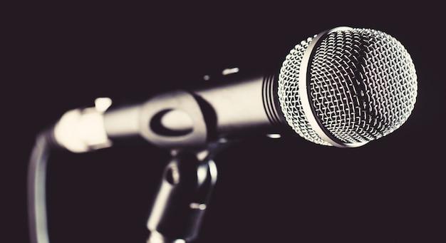 Microfone, microfone, karaokê, concerto, música de voz. microfone de áudio vocal em um fundo preto. cantora em karaokês, microfones. música ao vivo, equipamento de áudio. microfone de close up. concerto de karaokê, som de canto.