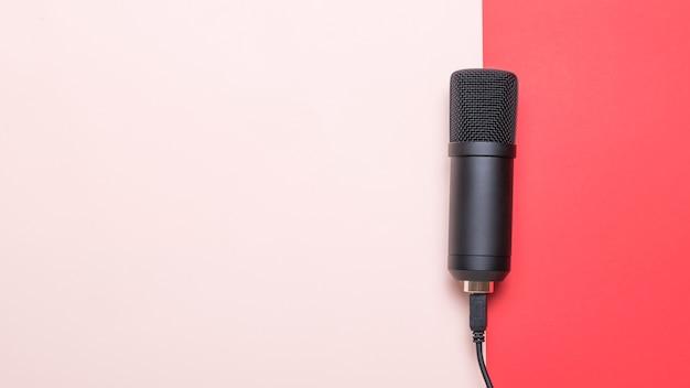 Microfone moderno e elegante na superfície vermelha e rosa. equipamento de gravação de som.