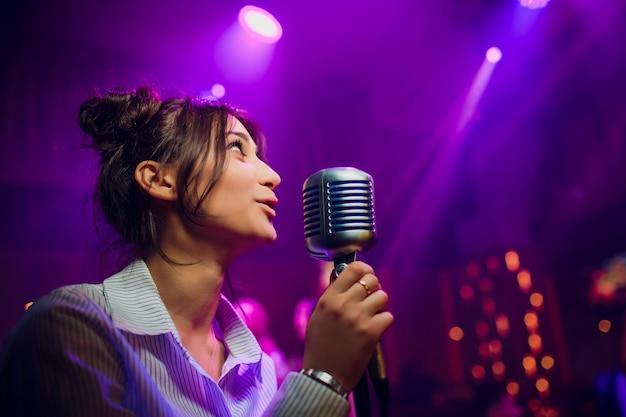 Microfone moderno para cantar contra o bokeh colorido embaçado bonito.