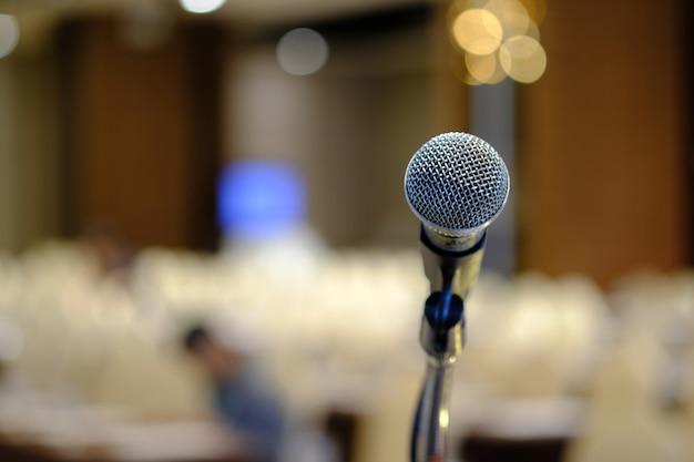 Microfone na frente de stand off luz turva quarto de reunião