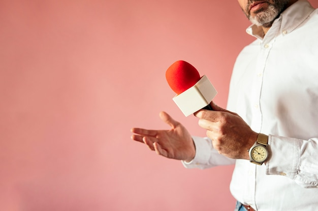 Microfone na mão de repórter com parede rosa