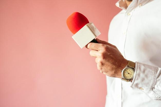 Microfone na mão do repórter com fundo rosa