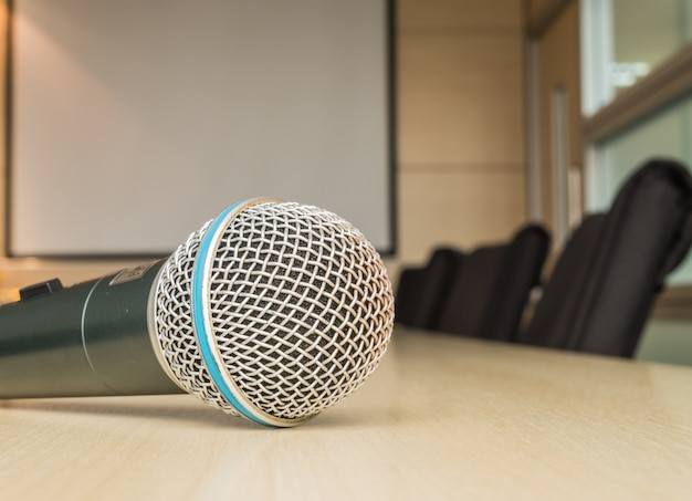 Microfone na mesa de madeira na sala de reuniões sob a luz da janela