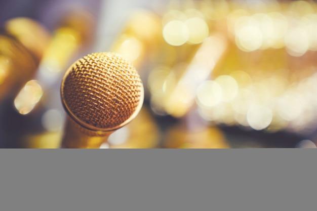 Microfone no borrão lindo fundo dourado bokeh