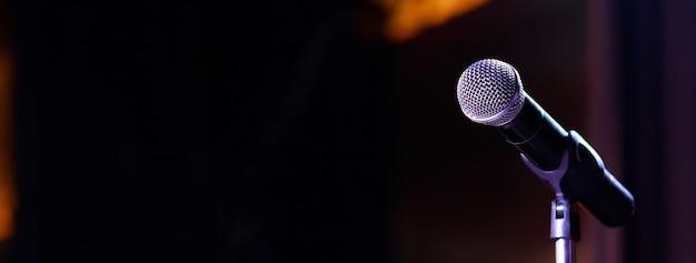 Microfone no desfoque abstrato da fala na sala de seminário ou luz da sala de conferências