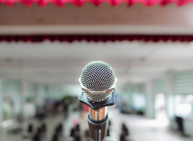 Microfone no palco contra um fundo de auditório.