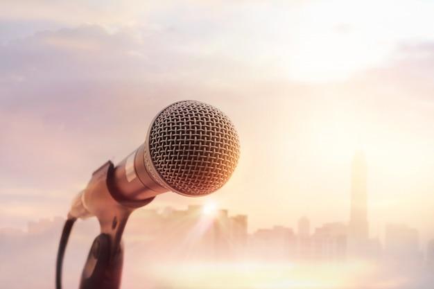 Microfone no palco da cidade no fundo por do sol