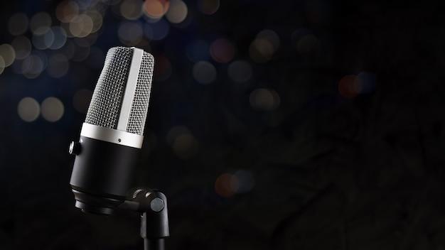 Microfone para gravação de áudio ou conceito de podcast, microfone único em fundo de sombra escura e bokeh com espaço de cópia