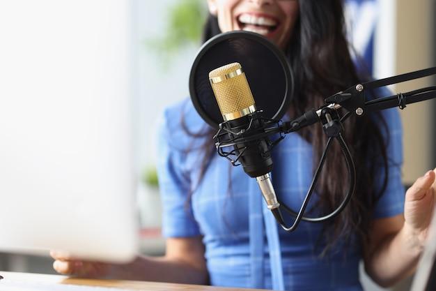 Microfone preto de estúdio ao fundo mulher canta aulas de canto para adultos conceito