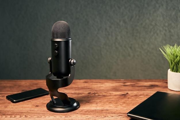 Microfone preto e dispositivos como um smartphone em uma mesa de madeira
