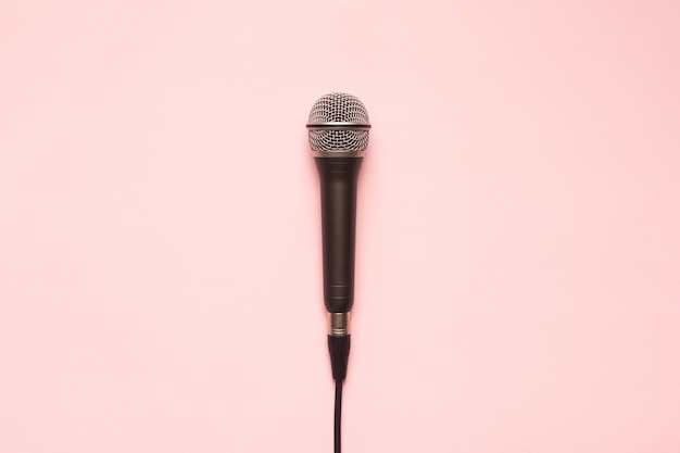 Microfone preto e prata em um fundo rosa