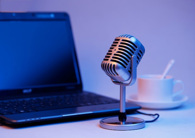Microfone retro e notebook, transmissão em tempo real no conceito de ar