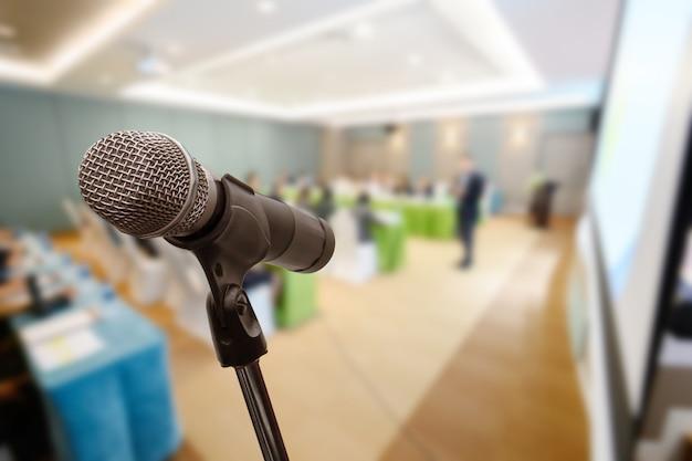 Microfone sobre o encontro borrado do fórum do negócio ou treinamento da conferência que aprende o conceito da sala de treinamento, fundo borrado.
