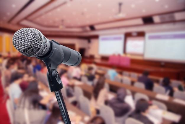 Microfone sobre os executivos borrados do fórum que encontra o treinamento da conferência que aprende o conceito de treinamento, fundo borrado.