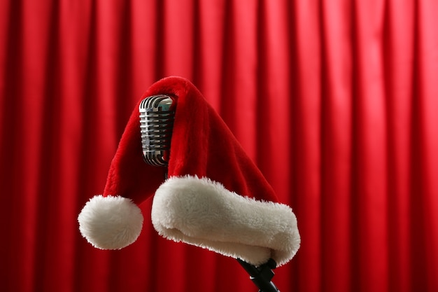Microfone vintage com chapéu de natal na superfície da cortina vermelha