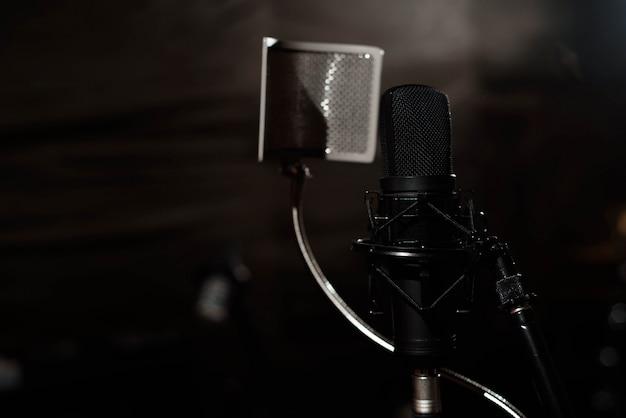 Microfone vocal preto está na sala de estúdio de gravação de som