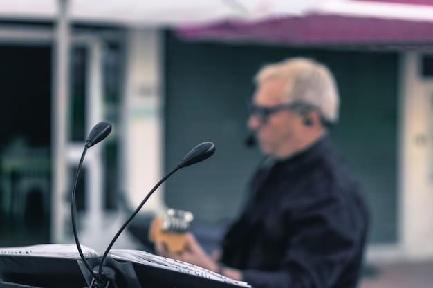 Microfones com um músico tocando violão desfocado no fundo