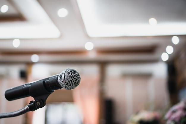 Microfones no desfoque abstrato da fala na sala de seminário