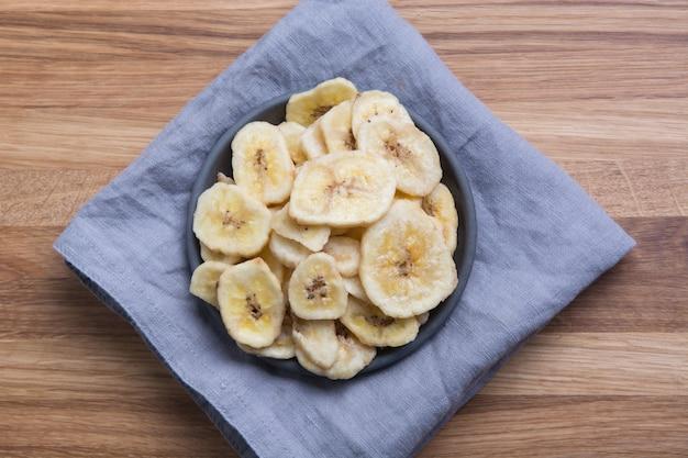 Microplaquetas de banana desidratadas, secas na placa de madeira. vista de cima.