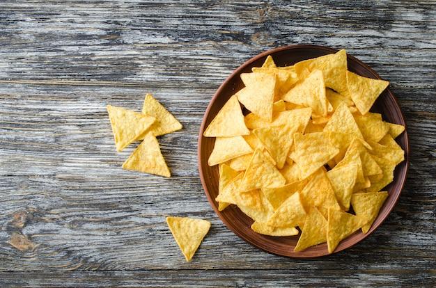 Microplaquetas de milho dos nachos em uma placa em uma tabela de madeira. conceito de comida mexicana.
