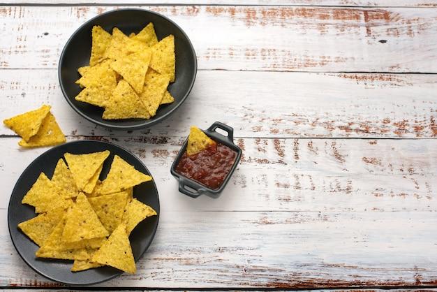Microplaquetas de milho nachos com salsa caseira fresca na mesa de madeira clara. vista do topo