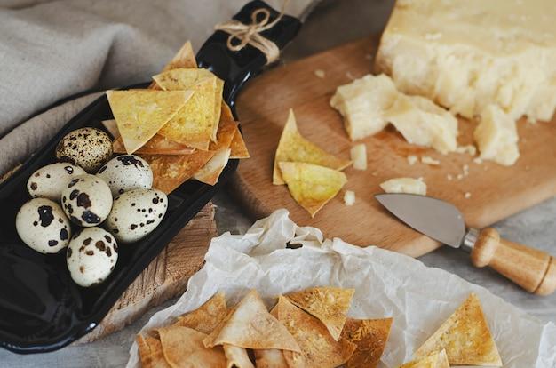 Microplaquetas friáveis caseiros do flatbread com queijo parmesão e ovos de codorniz na placa do serviço feita da garrafa.