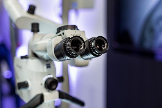 Microscópio dental no fundo da odontologia moderna. equipamento médico. microscópio cirúrgico odontológico com binóculo duplo rotativo.
