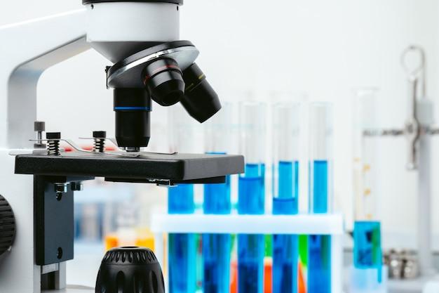 Microscópio e tubos de ensaio na mesa em laboratório, close-up