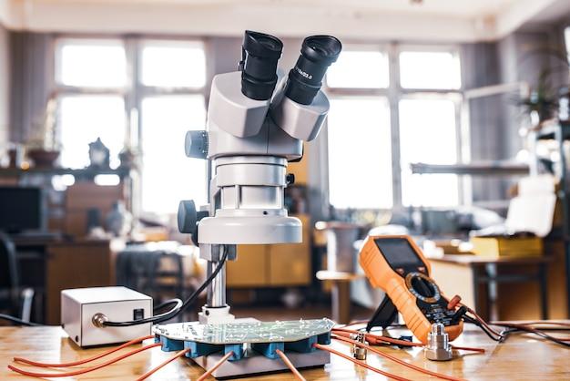 Microscópio moderno, componente de conectores e grande microcircuito verde em laboratório de oficina