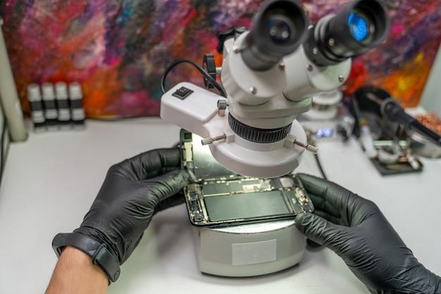 Microscópio no qual o mestre examina um smartphone desmontado com defeito