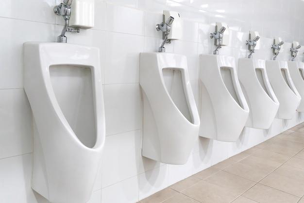 Mictório branco no banheiro masculino.