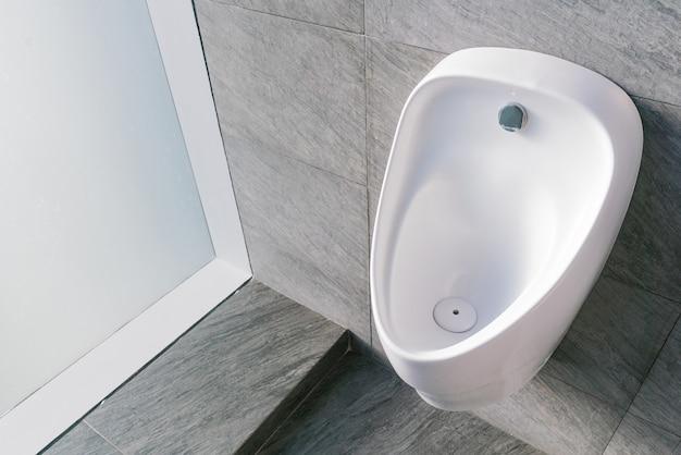 Mictório de cerâmica branca no banheiro masculino com lavador eletrônico higiênico de economia de água.