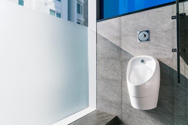 Mictório de cerâmica branca no banheiro masculino