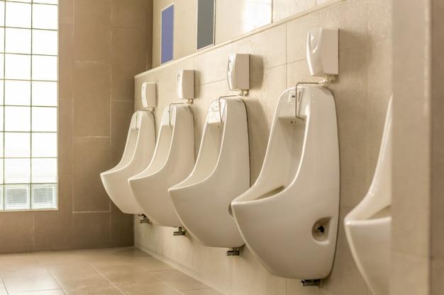 Mictórios brancos em seguido no toalete público dos homens.