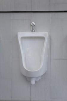Mictórios brancos no banheiro masculino de decoração de interiores.