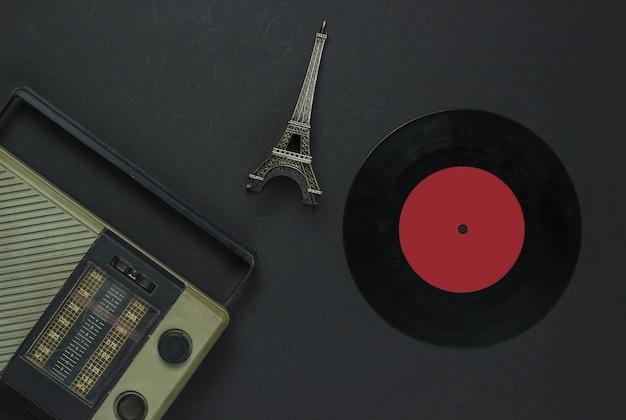 Mídia retro. receptor de rádio, disco de vinil, estatueta da torre eiffel em um fundo preto. vista do topo.