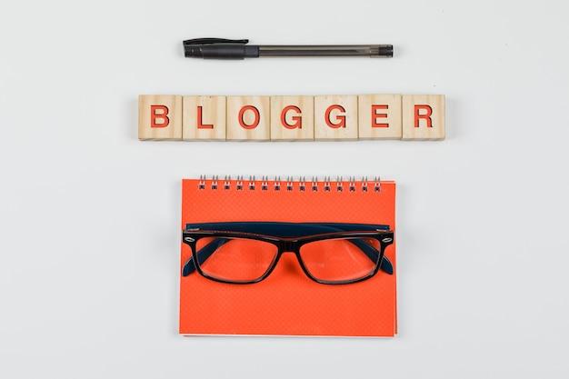 Mídia social e conceito do negócio com blocos de madeira, caderno espiral, óculos, caneta na configuração de plano de fundo branco.