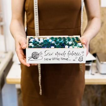 Midsection vista da mão do designer de moda segurando o recipiente cheio de tópicos