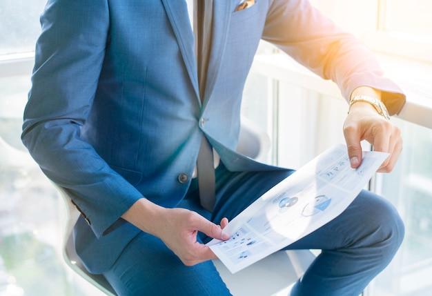 Midsection, vista, de, um, homem negócios, mão, segurando, infográfico, folha
