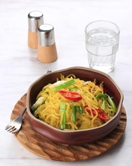 Mie glosor ou mie gelosor. glossy yellow noodles populares em bogor, west java. macarrão feito de tapioca ou farinha de sagoo (aci) misturado com cúrcuma, takjil popular para o café da manhã no ramadã.