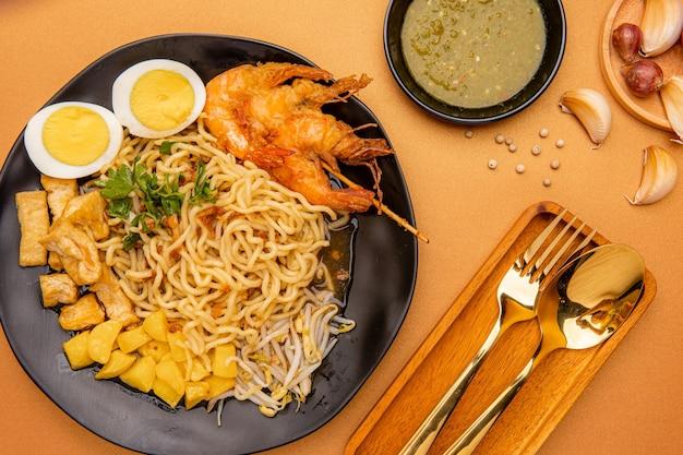 Mie rebus medan ou sopa de macarrão o prato é feito de macarrão de ovo amarelo que também é usado em hokkien mee com um molho picante ligeiramente doce semelhante ao curry. o molho é feito de caldo de camarão ou tauchu
