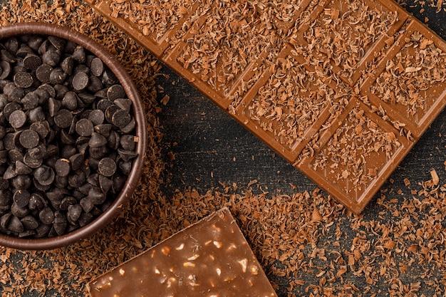 Migalhas de chocolate com barras de chocolate e gotas de chocolate