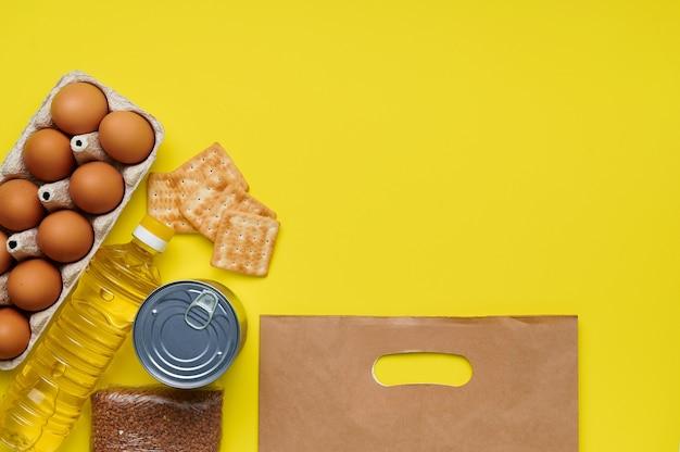 Migalhas de pão, biscoitos, trigo sarraceno, ovos, produtos enlatados, saco de papel de óleo de girassol no fundo amarelo
