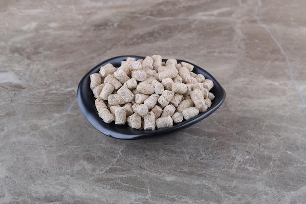 Migalhas de pão na tigela, na superfície do mármore