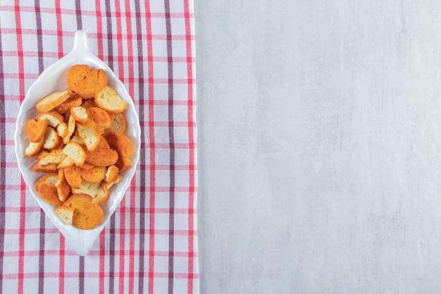 Migalhas secas crocantes no prato em forma de folha com toalha de mesa listrada.