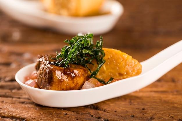 Mignon de porco com canjiquinha cremosa e vinagrete na colher. prove petiscos gastronômicos