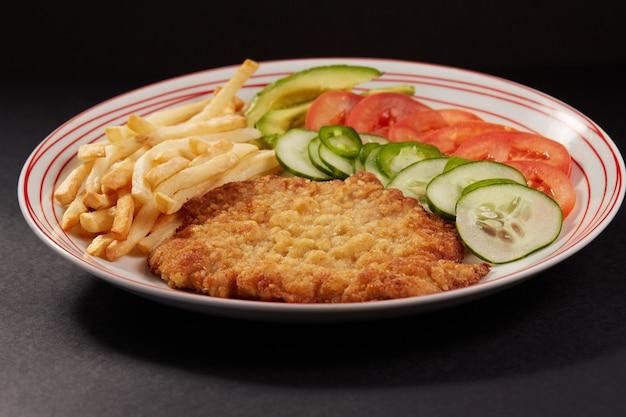 Milanesa de pollo com papas fritas y ensalada de pepino tomate y aguacate