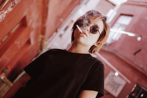 Milenar garota bonita legal com cabelo ruivo curto e óculos de sol espelhados fumando cigarro na cidade velha com paredes vermelhas