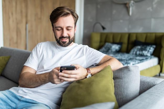 Milenar homem sentado na sala no sofá em casa sorrindo conversando digitando mensagem usando celular.