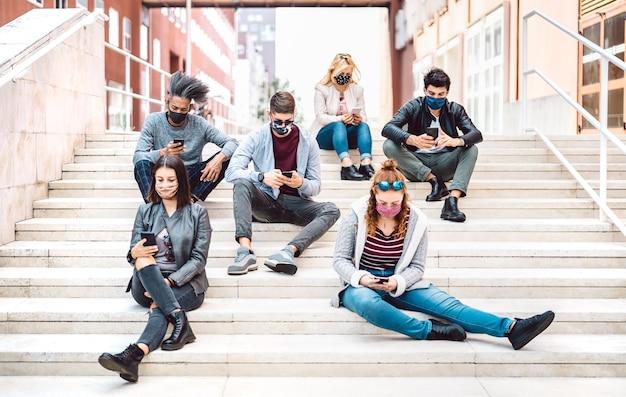 Milenares urbanos usando telefones celulares cobertos por máscara facial na terceira onda de covid